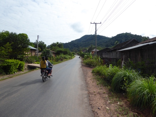 Moped driving through typical Laos village
